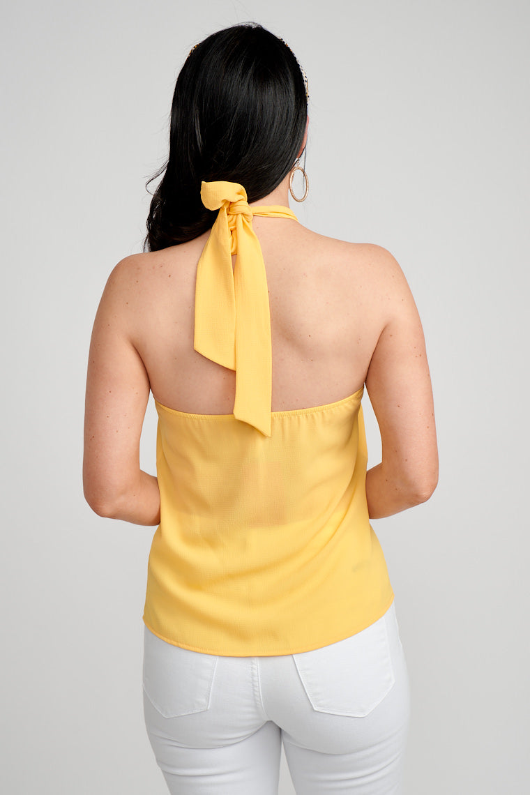 This sleeveless halter top has a fabric tie supporting a twisted top with keyhole detail at the neckline and leads down to a relaxed bodice silhouette that meets at the waist.