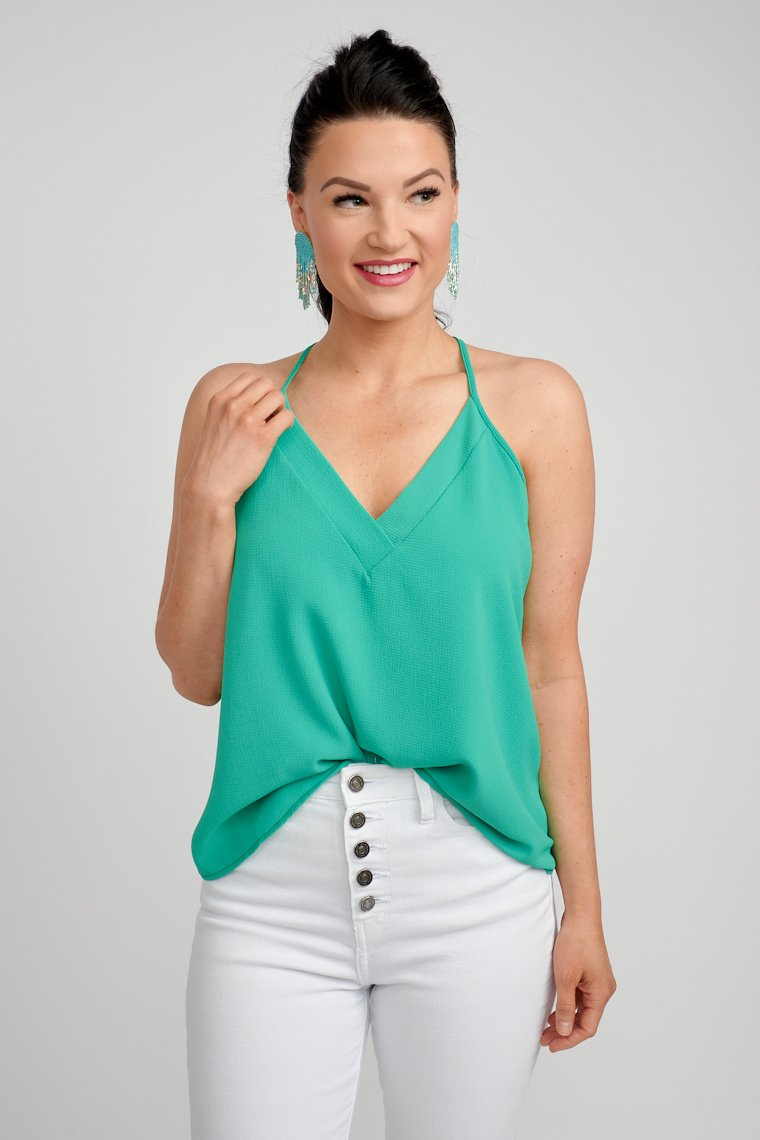 Racerback tank top has thin straps that attach to a banded v-neckline on a relaxed-fit bodice silhouette that meets at the waist. Style with white skinny jeans.