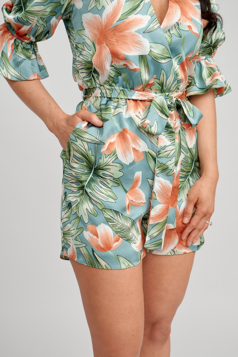 Mid-length elastic ruffle sleeves attach to a surplice neckline on a comfortable fit bodice silhouette that meets an elastic waistband and goes down to pocketed relaxed shorts.