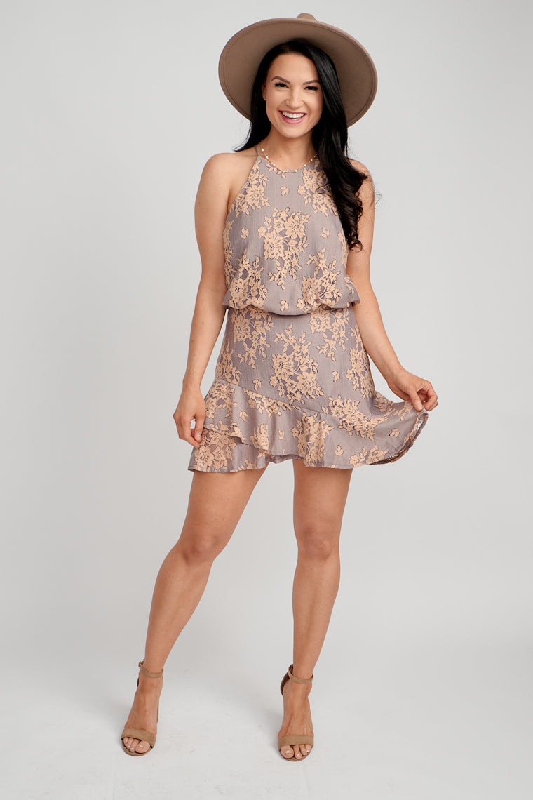 Lace floral prints across its fabric with a high neckline that leads to a relaxed bodice that meets a fitted waistband and into an a-line skirt with an asymmetrical ruffle.