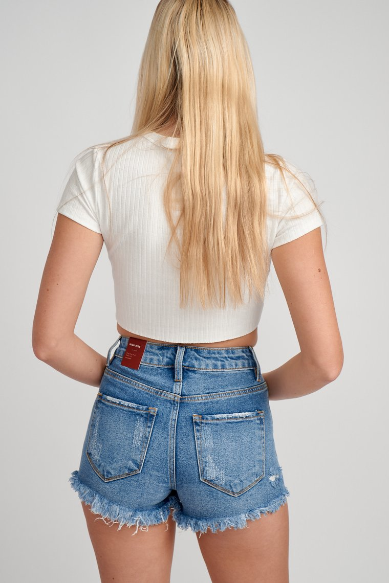 These medium wash shorts have a button and belt loop waistband with a traditional 5-pocket structure with a zipper fly that leads to distressed with a frayed cut-off hem.