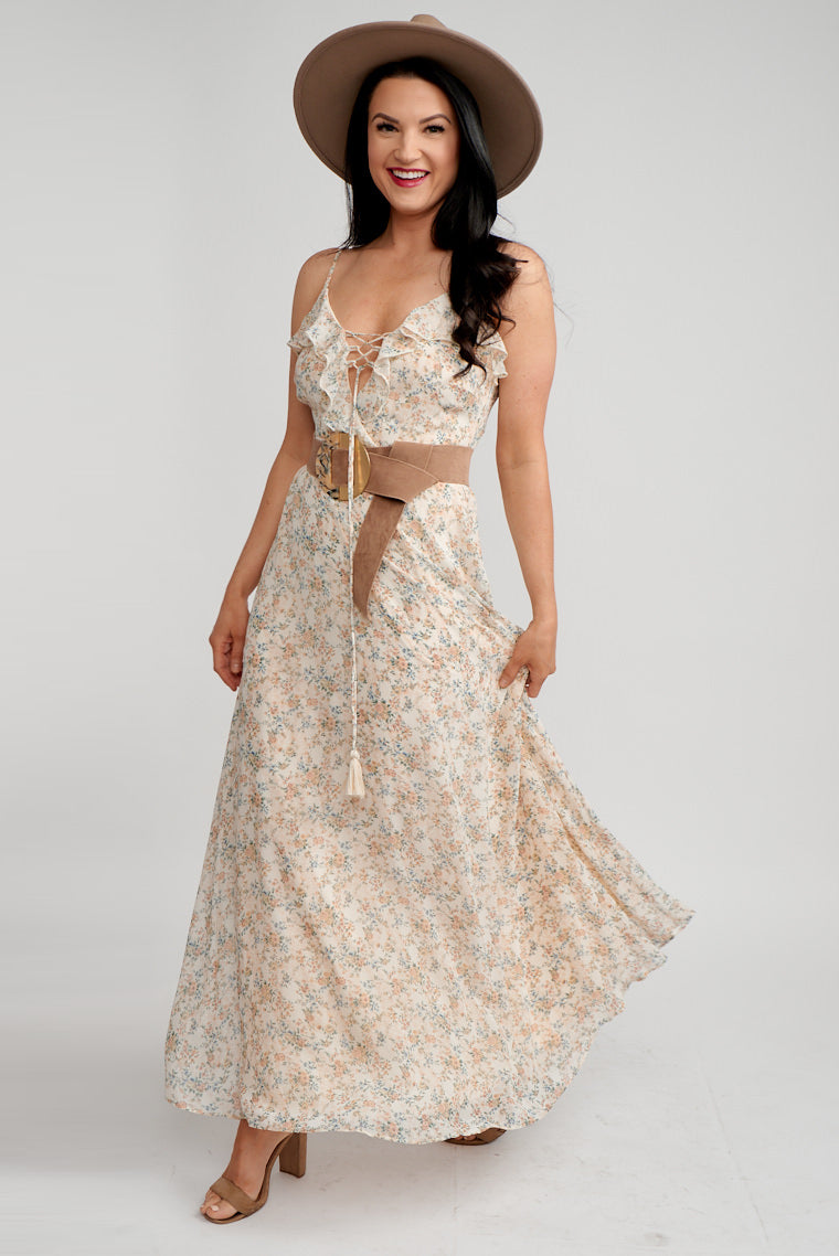 Thin adjustable straps attach to a ruffled surplice neckline with a crisscrossed detail on fitted bodice that meets a fitted waistband and flows down into a long maxi skirt