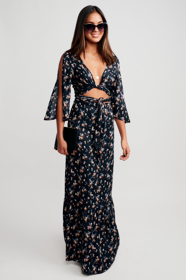 This flower-speckled maxi dress has long split sleeves and has a v-neckline with a tie-front that hangs over a bare midriff into a long and flowy skirt.