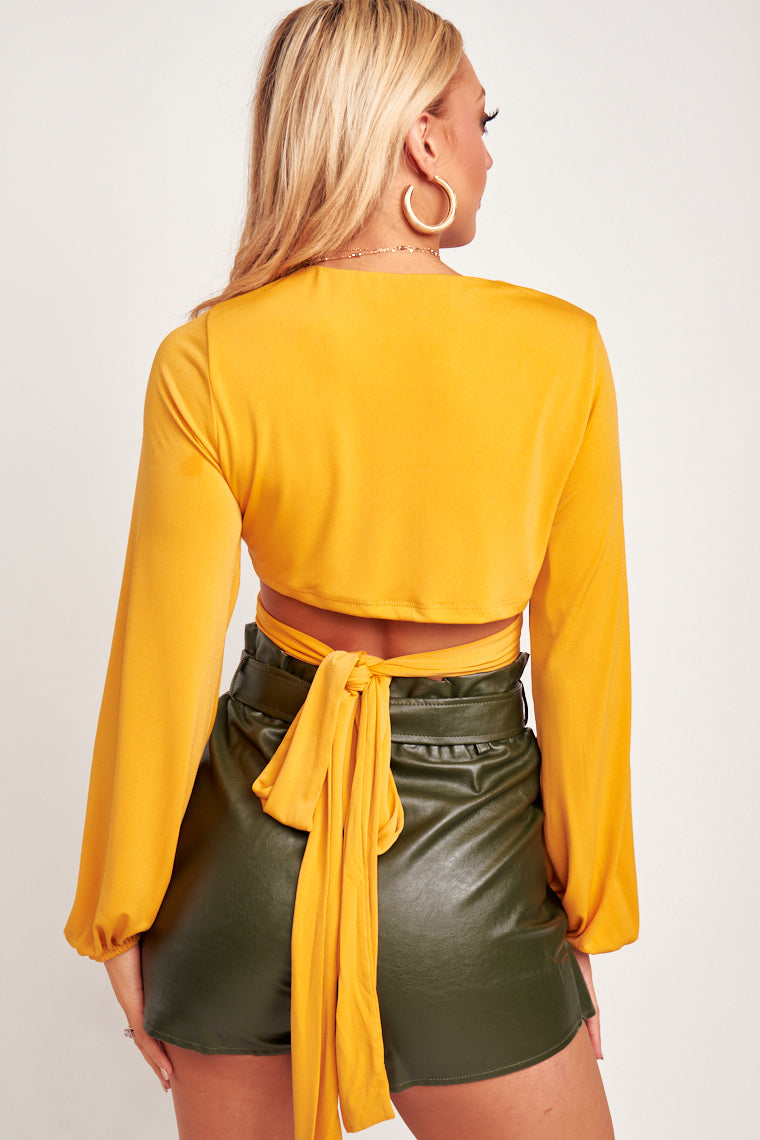 This mustard top is long-sleeved with an elastic cuff and has a deep v-neckline leading to circle ring with fabric pieces to wrap and tie at the midriff.