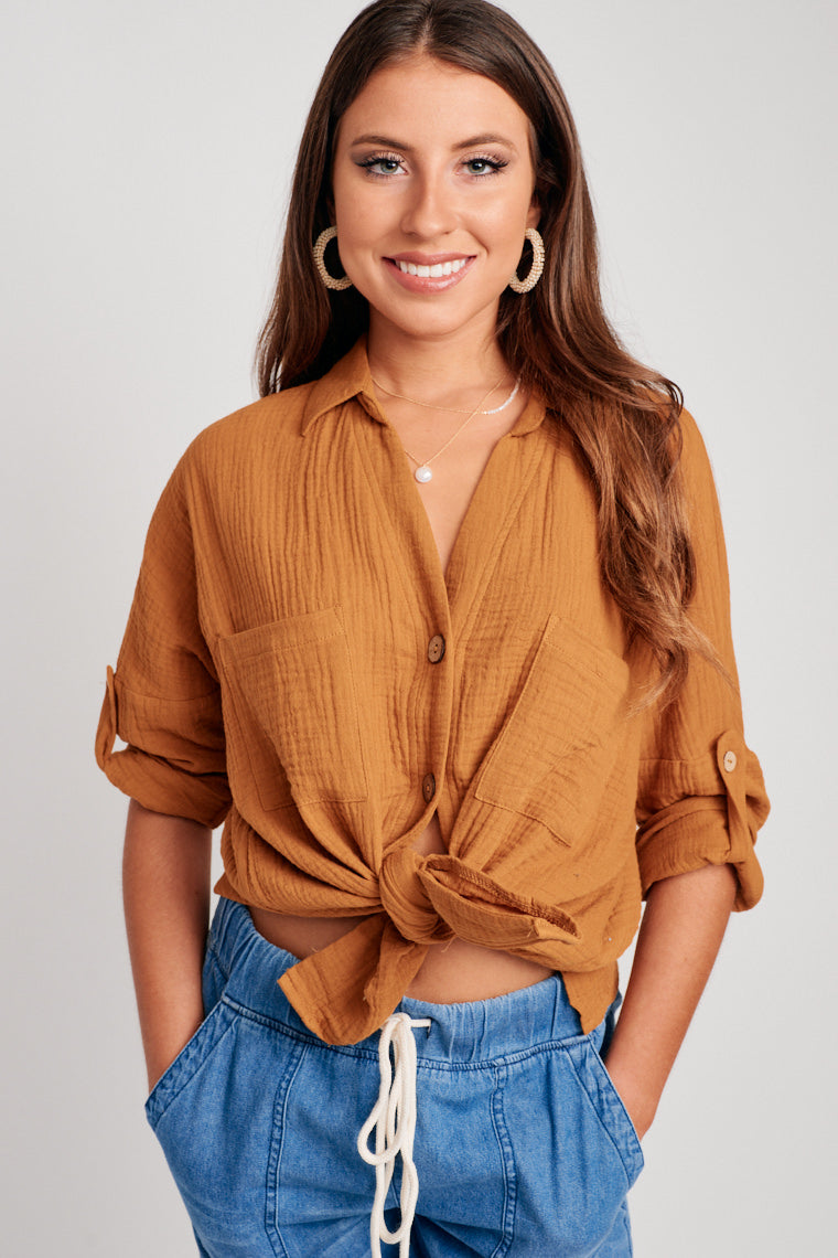 This collared top has long cuffed sleeves that attach to a banded button-down and oversized bodice with front pockets. The sleeves of the top could roll up.