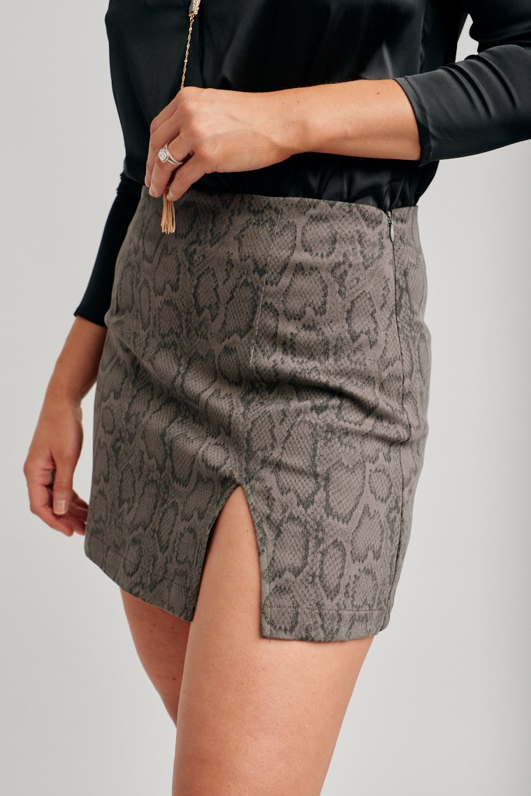 Faded black snake print covers this comfortable skirt. The skirt has a fitted waistband and leads to a darted and mini pencil silhouette with a slit at the side of the panel.