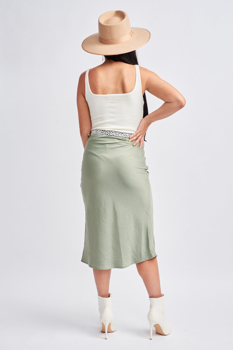 This satiny skirt has an elastic waistband that leads into a fitted then flowy skirt silhouette that meets mid-calf. Style with a white bodysuit.