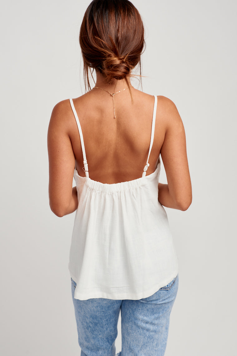 This top has skinny adjustable straps that attach onto a gentle box pleated neckline that drapes an oversized bodice silhouette. Pair this with medium wash jeans.