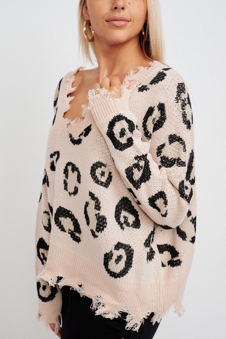 This leopard patched sweater has long sleeves is attached to a v-neckline with distressed trim. It leads down to a comfortable and cropped bodice silhouette.