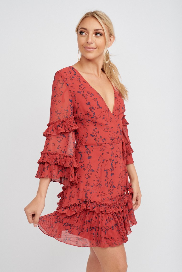 Mid-length accordion pleat ruffled sleeves that attach to a surplice neckline on a fitted bodice and goes down to a flowy skirt with an accordion pleat ruffle hem.