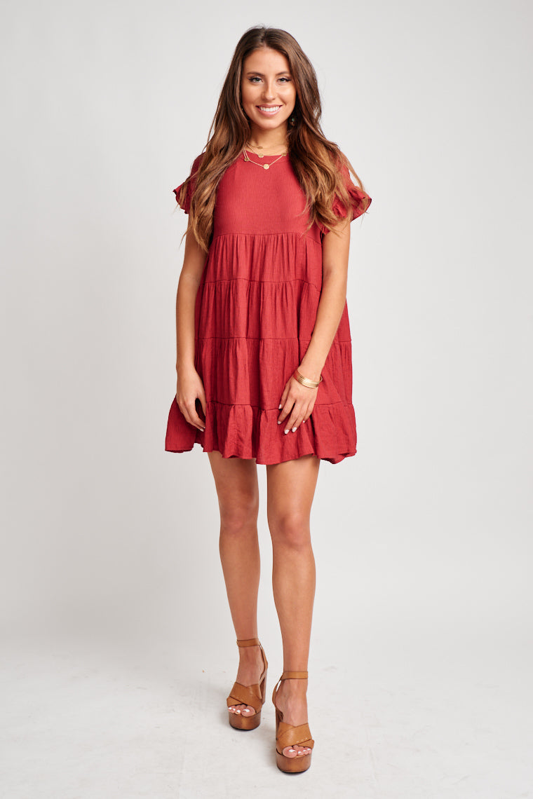Crew neckline with short ruffle sleeves attaches to an oversized bodice with a tiered ruffle swing skirt. This dress features a button closure at the neck on the back.