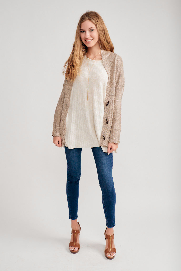 Long sleeves that attach to a collared v-neckline neckline which leads to a slouchy silhouette with duffle buttons down the front and meets at the bottom of the hips.
