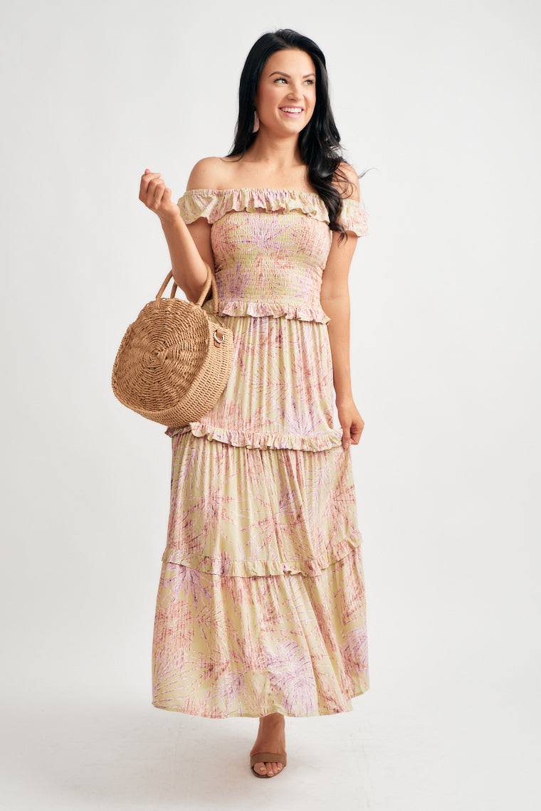 Printed maxi features an off the shoulder, ruffled neckline that flows into a smocked bodice atop a flowy, tiered maxi skirt with whipped cream, ruffle accents.
