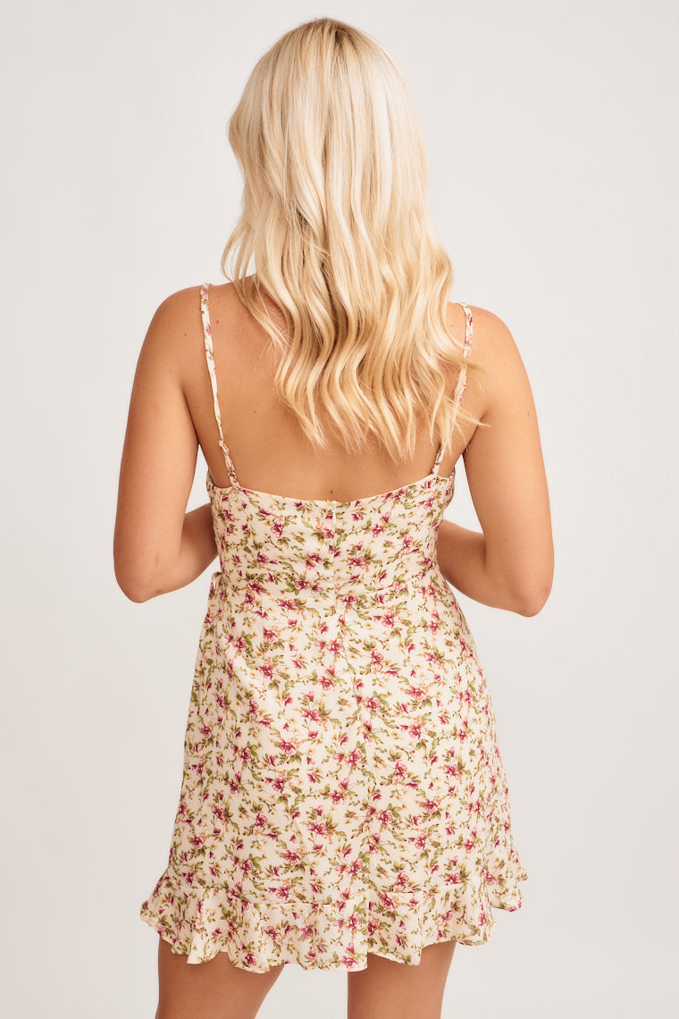 This lightweight dress has flowers, surplice neckline, fitted waistband, and a flowy asymmetrical skirt that ties on the side and ruffles at the hem.