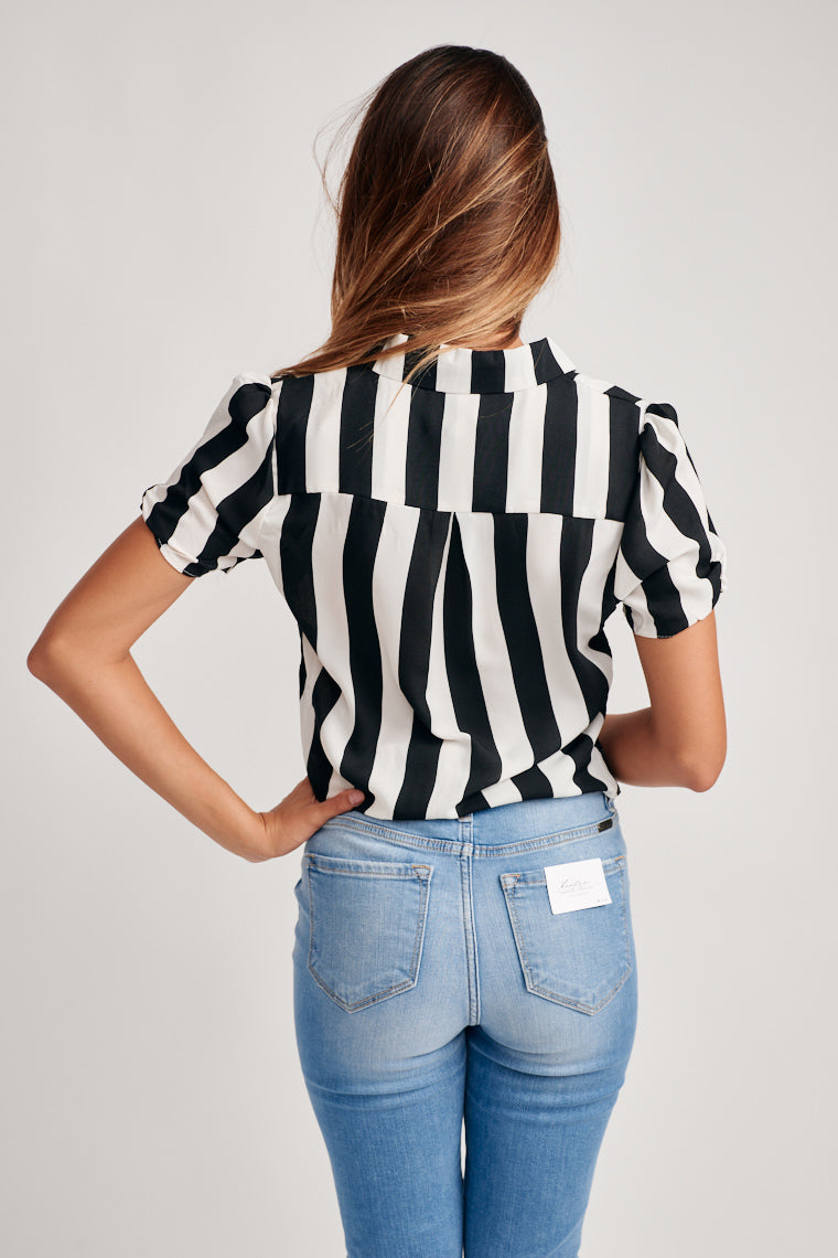 Black and white stripes decorate this lightweight, short sleeve top. The collared neckline moves into a button-down center with a semi-cropped hem.