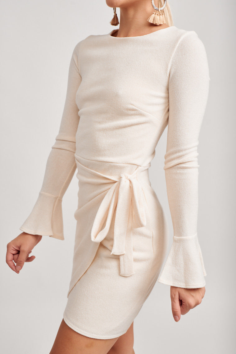 Long fitted long sleeves with a baby bell cuff attach to a high u-neckline and fitted bodice and lead down to a skirt panel that ties at the side atop of a fitted skirt.
