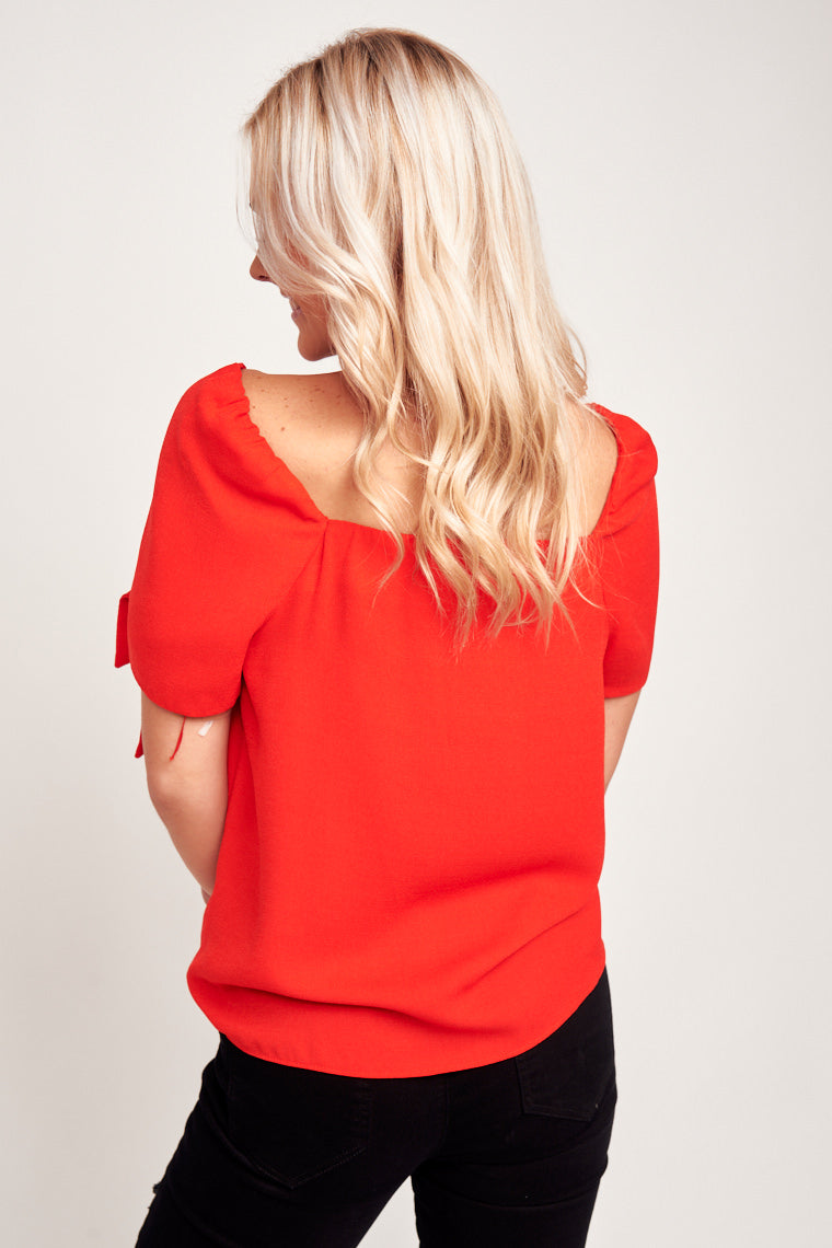 This red top has short tie puff sleeves that attach to a square neckline and has a relaxed bodice. Style by tucking into a skirt or let it flow free with a pair of jeans.
