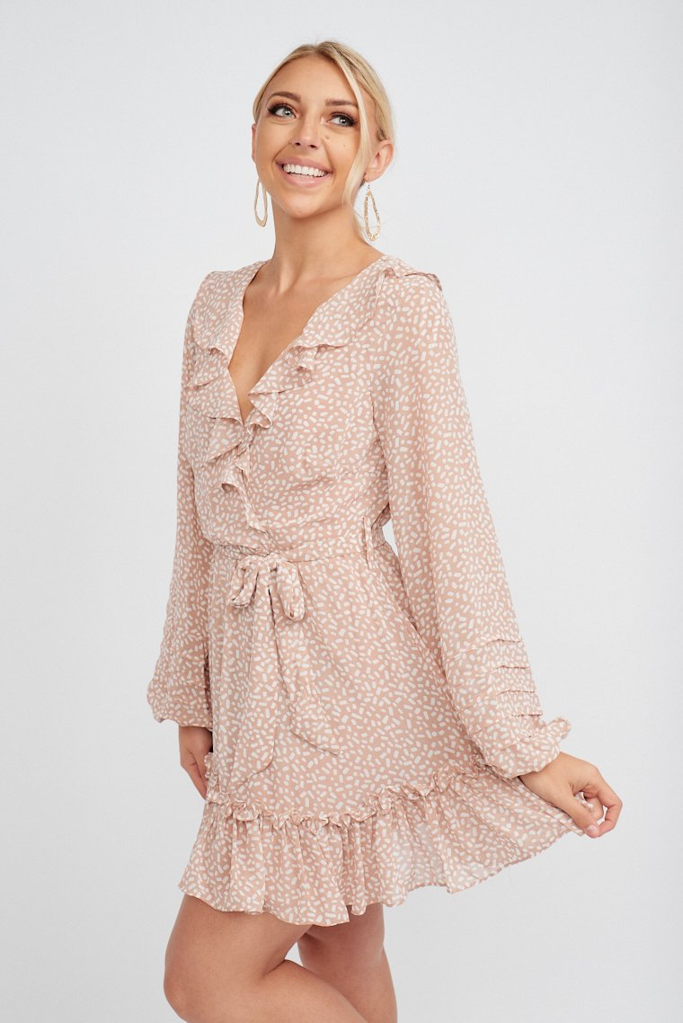 Long elastic sleeves attach to a surplice neckline with a ruffled hem on a relaxed bodice and leads to a fitted waistband and flows down to a mini skirt with a ruffle hem.