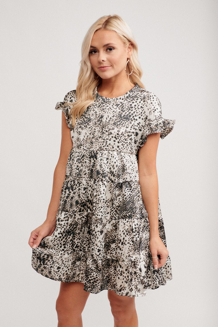 Black prints speckle this shiny fabric dress. It has a crew neckline with short ruffle sleeves attaches to an oversized bodice with a tiered ruffle swing skirt.