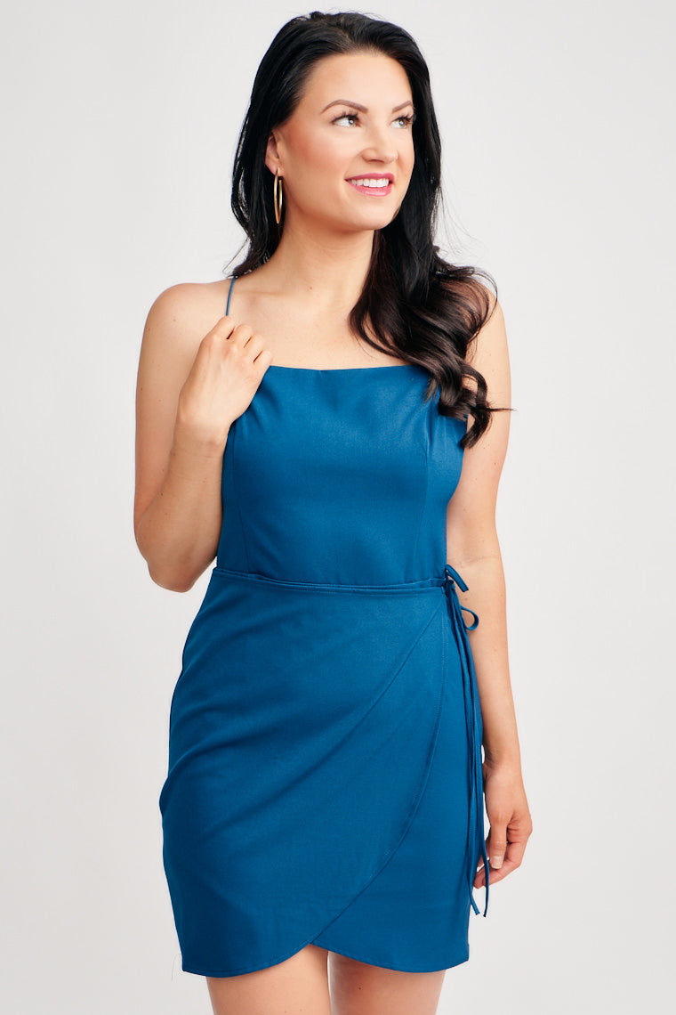 This teal dress offers a straight neckline, darted bodice, a keyhole open back, and wrapped skirt that ties at the side. This dress features button keyhole closure.