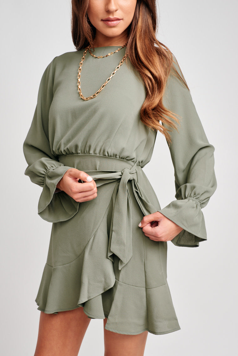 Long elastic cuff sleeves with a flounced hem and attaches to a high straight-neckline relaxed bodice and skirt is flowy and has a panel that wraps over.
