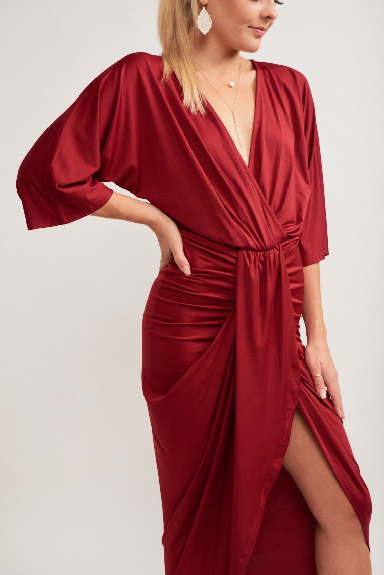 Mid-length relaxed fit sleeves attach to a surplice neckline and a comfortable bodice silhouette leads to a fitted waist and drapes over asymmetrical skirt.