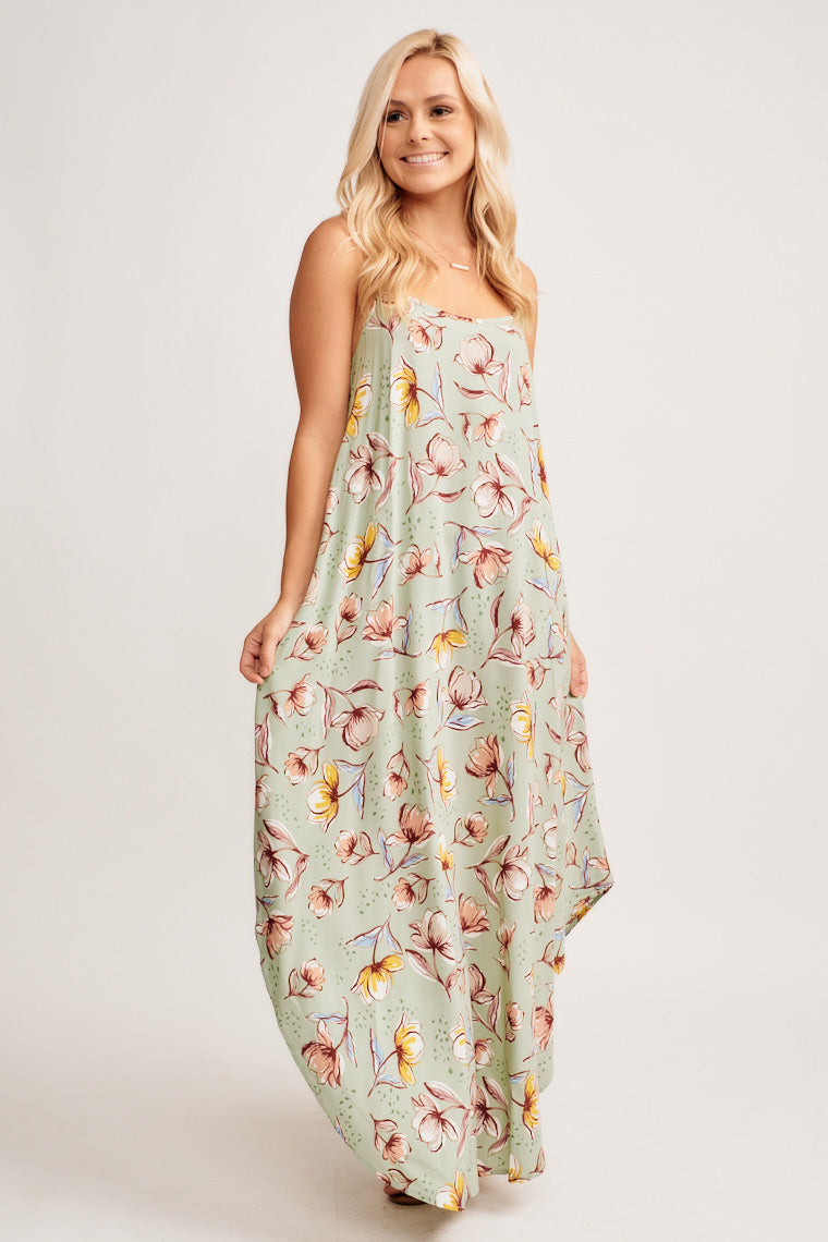 This sage dress is decorated in flowers outlined in black. This maxi dress has thin straps and a gentle scoop neckline which leads into a relaxed and flowy silhouette.