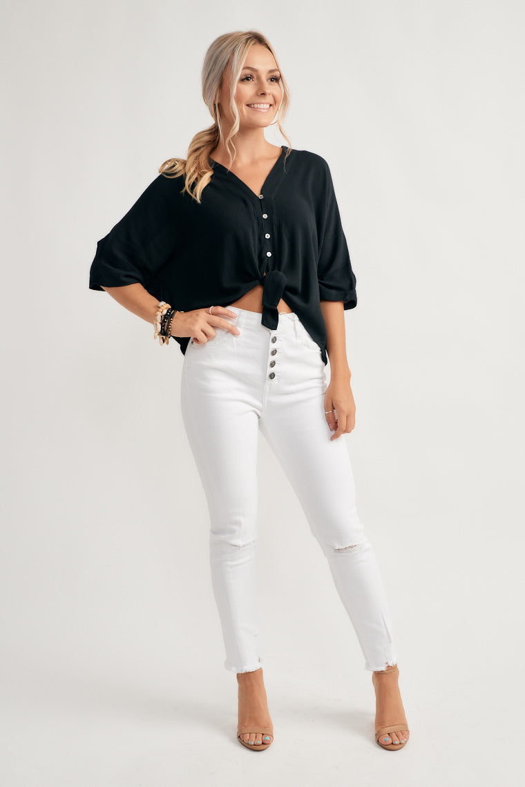 This black lightweight blouse features dolman short sleeves on a v-neckline with a button-up center bodice with a relaxed silhouette and tie-front hem.