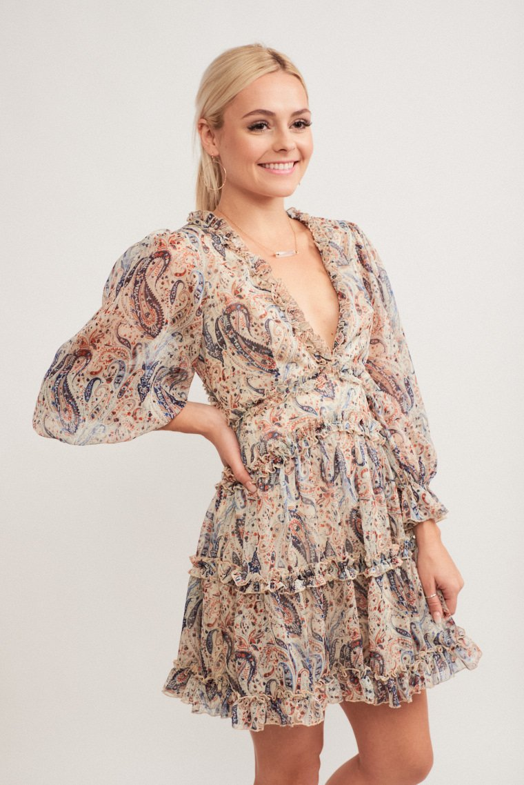 Paisley printed dress has long elastic ruffle sleeves that lead to a deep v-neckline leads into a fitted bodice and waistband and flows into a tiered ruffle skirt.