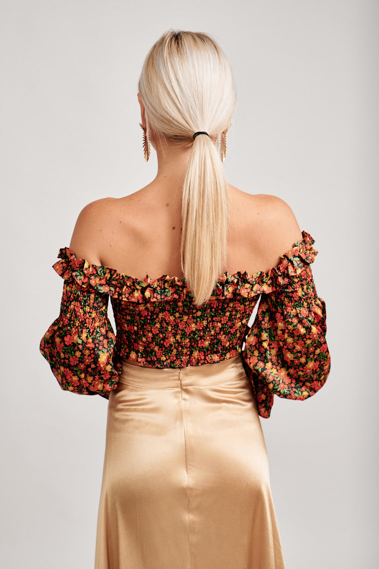 Multi-colored flowers cover long puffed elastic cuff sleeves attach to an off the shoulder straight neckline with a ruffle hem and goes into a fitted smocked and cropped bodice.