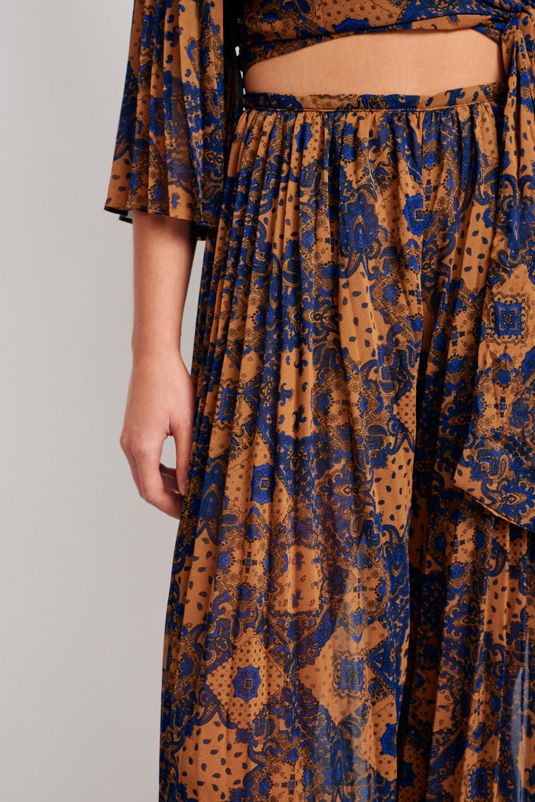 Sheer paisley patterned fabric lays atop of solid short insert with a fitted waistband and flows into pleated and flowy pant legs.