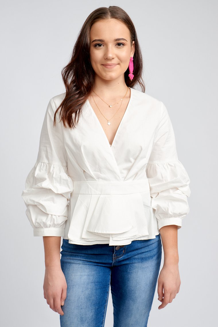 Mid-length tier puffed sleeves attach to a surplice neckline on a relaxed bodice silhouette and lead to a banded waist that flares into a peplum style hem.