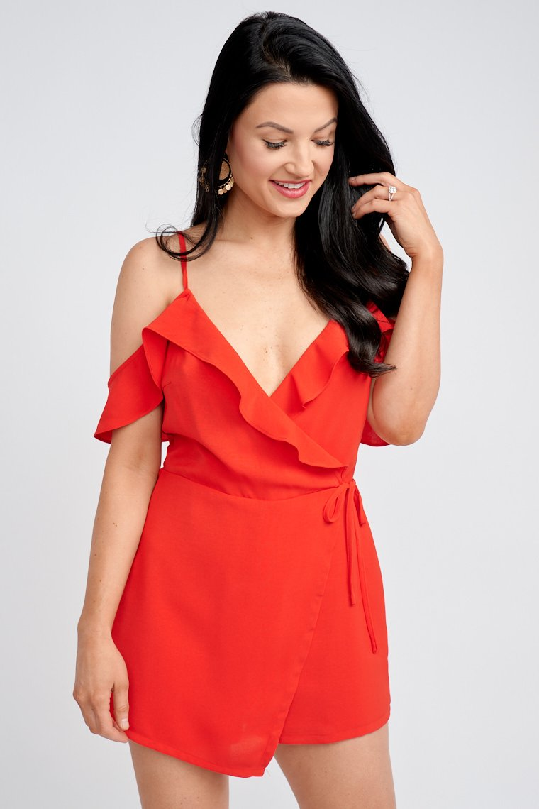 Thin adjustable straps attach to a surplice ruffled neckline with flutter sleeves, relaxed bodice silhouette leads to relaxed shorts under a skirt panel that ties at the side.