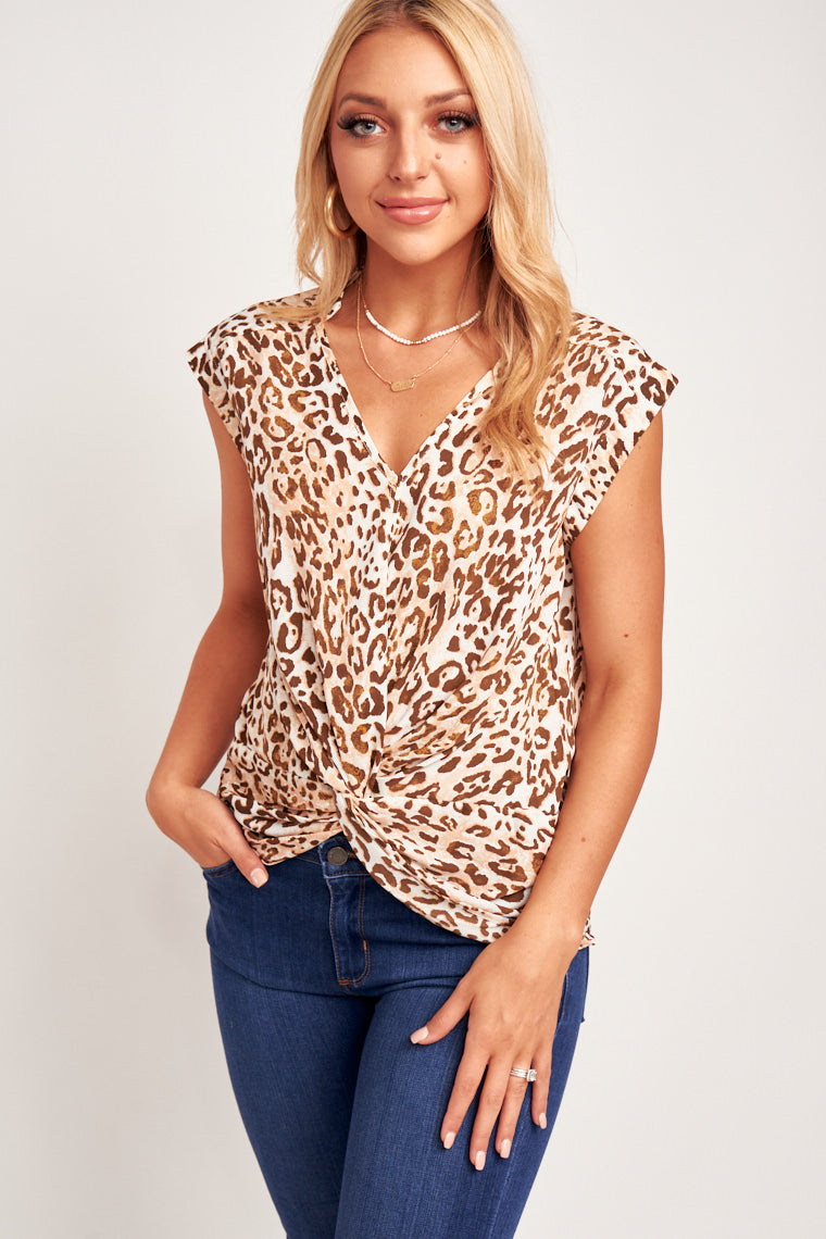 Brown leopard spots scatter across this short-sleeved and relaxed flowy bodice. This top has a charming twist front detail at the bottom!