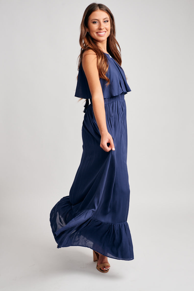 Thin straps attach to a high u-neckline flounce bodice leading to an elastic waistband and flow into a long maxi skirt with tiered ruffle hem. The strap has tassels details.