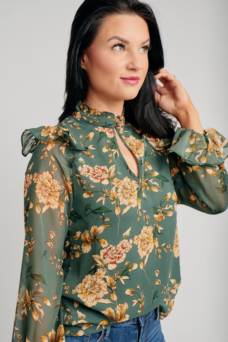 Multicolored flowers decorate the lightweight fabric, long elastic cuff sleeves with ruffles attached to high banded and buttoned neckline into a comfortable oversized bodice.