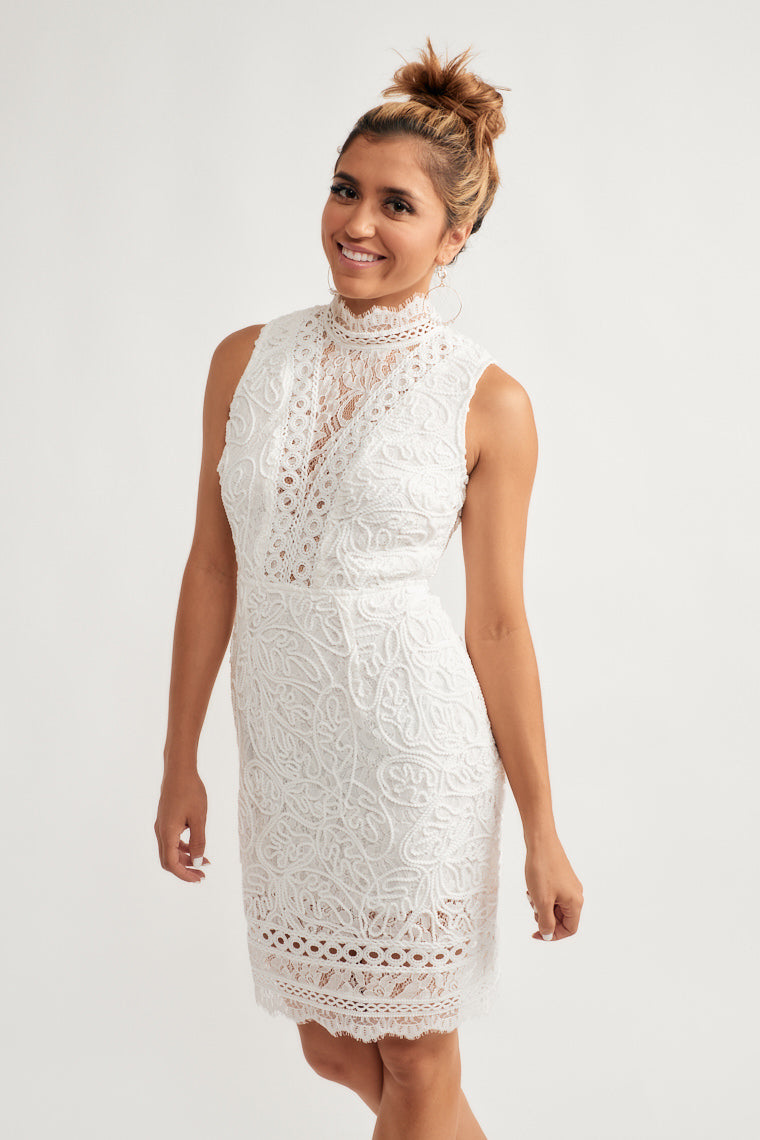 This stunning lace mini dress features a high, laced turtle neckline that moves into a fully laced, sleeveless bodice and a fitted waist with a figure flattering mini skirt.
