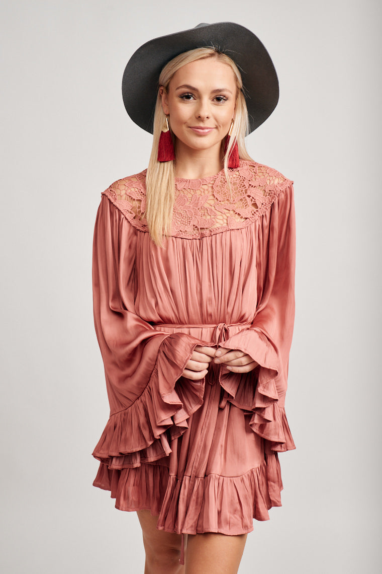 Long flowy ruffled bell sleeves attach to a high lace neckline that lays atop a comfortable and loose bodice silhouette and leads to a skirt with a ruffle hem.