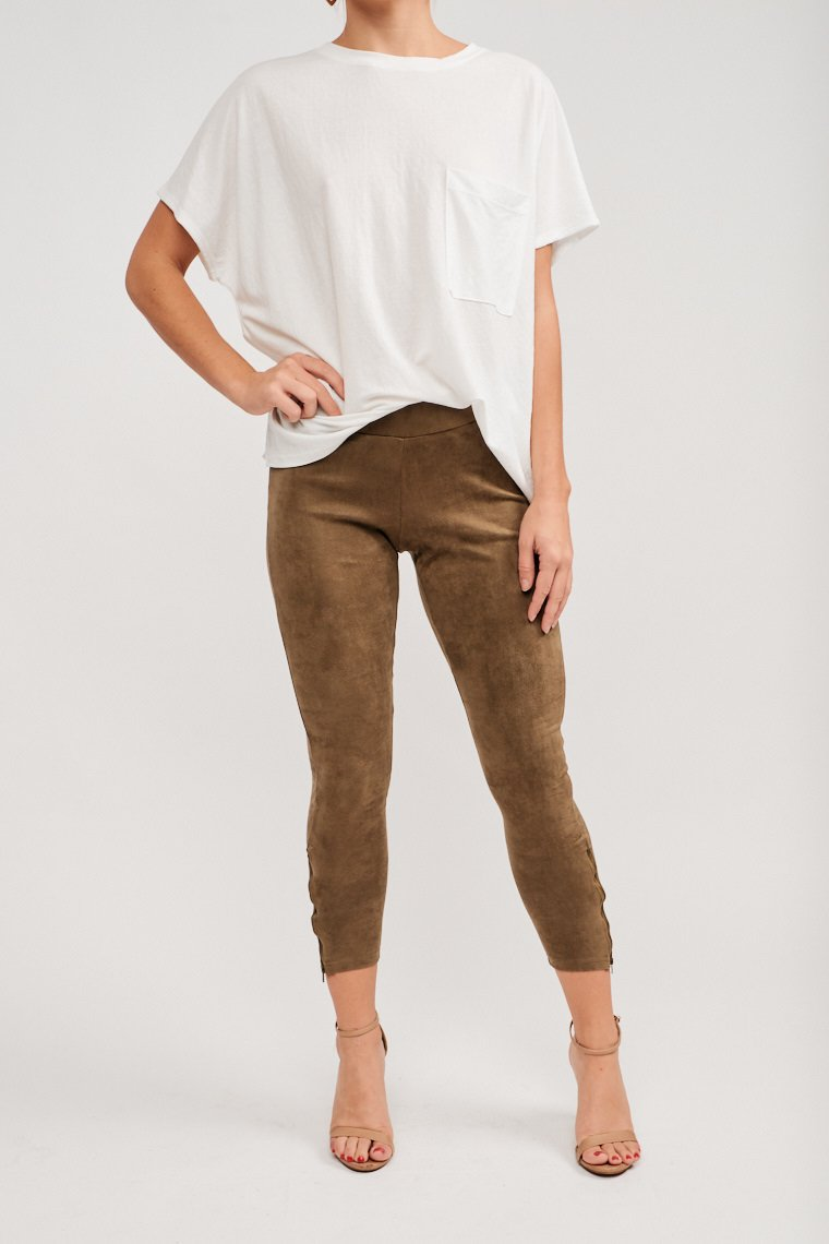 These pants have an elastic waistband that attaches to a fitted waist and pant legs with zipper details at the ankle. Pair with an oversized tee and a layered necklace.