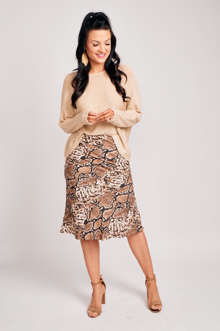 This brown and black snake print skirt is lightweight and has a fitted waistband that leads to gentle flair at the hem. This skirt features a zipper with a hook and eye closure.