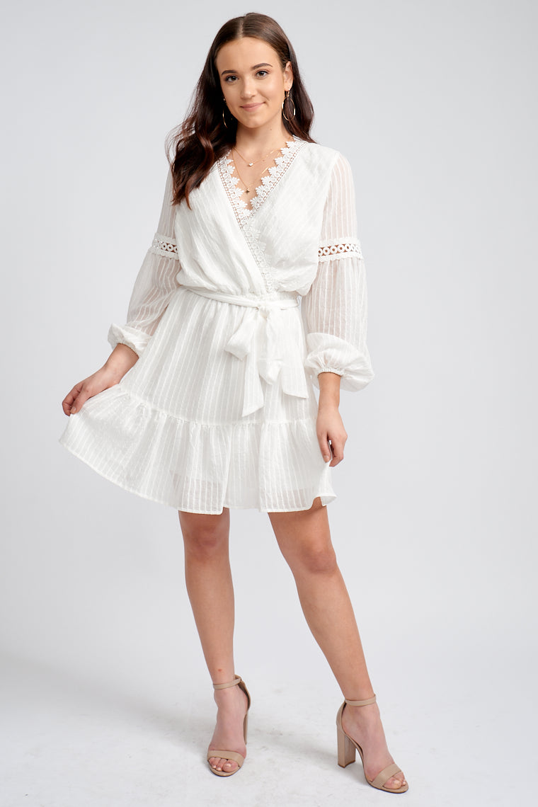 Long elastic cuff sleeves attaches to a surplice neckline with a crochet scalloped hem bodice flows down to a simple a-line skirt with a ruffle hem at the bottom.