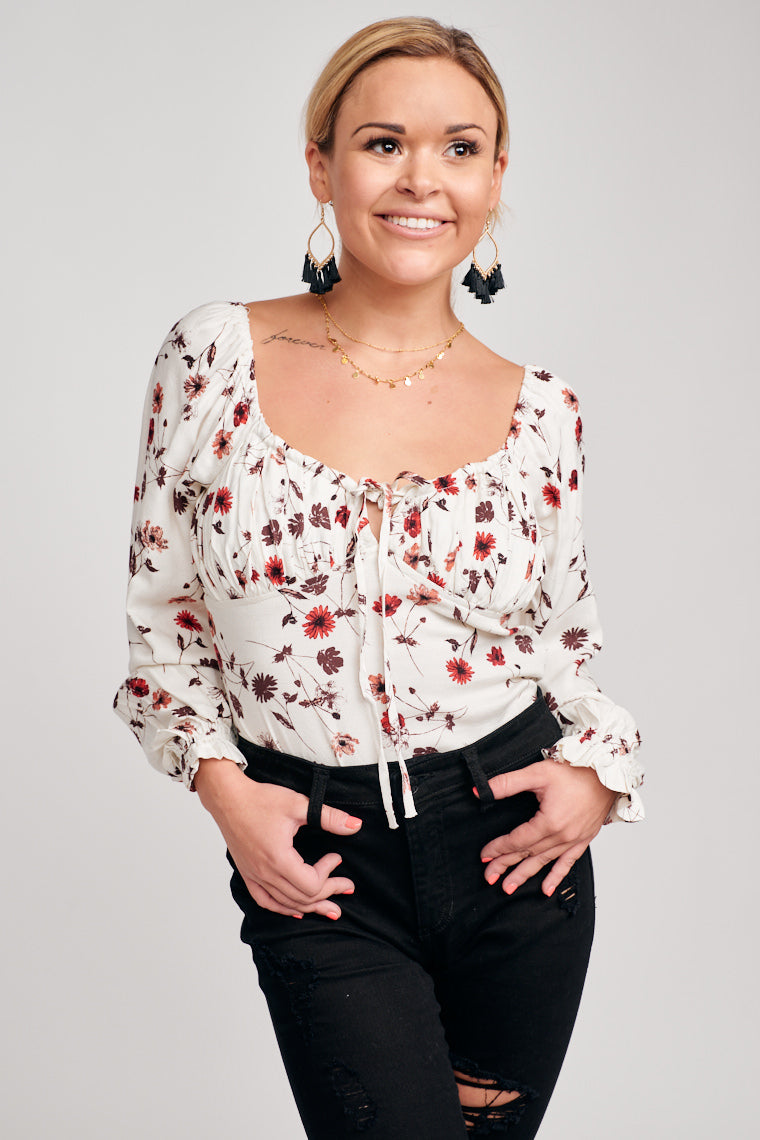 The peasant-style top with elastic cuffed and ruffle long sleeves lead to a v-neckline and shirred bust panel with a tie that connects to a relaxed, cropped bodice.