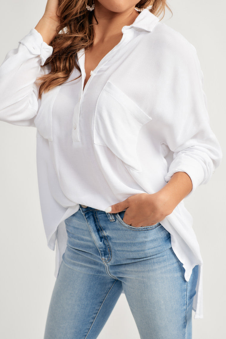 This white lightweight blouse features a three, button-up bodice with a collared-neckline, two front pockets on a relaxed silhouette and long sleeves, rolled to a button.