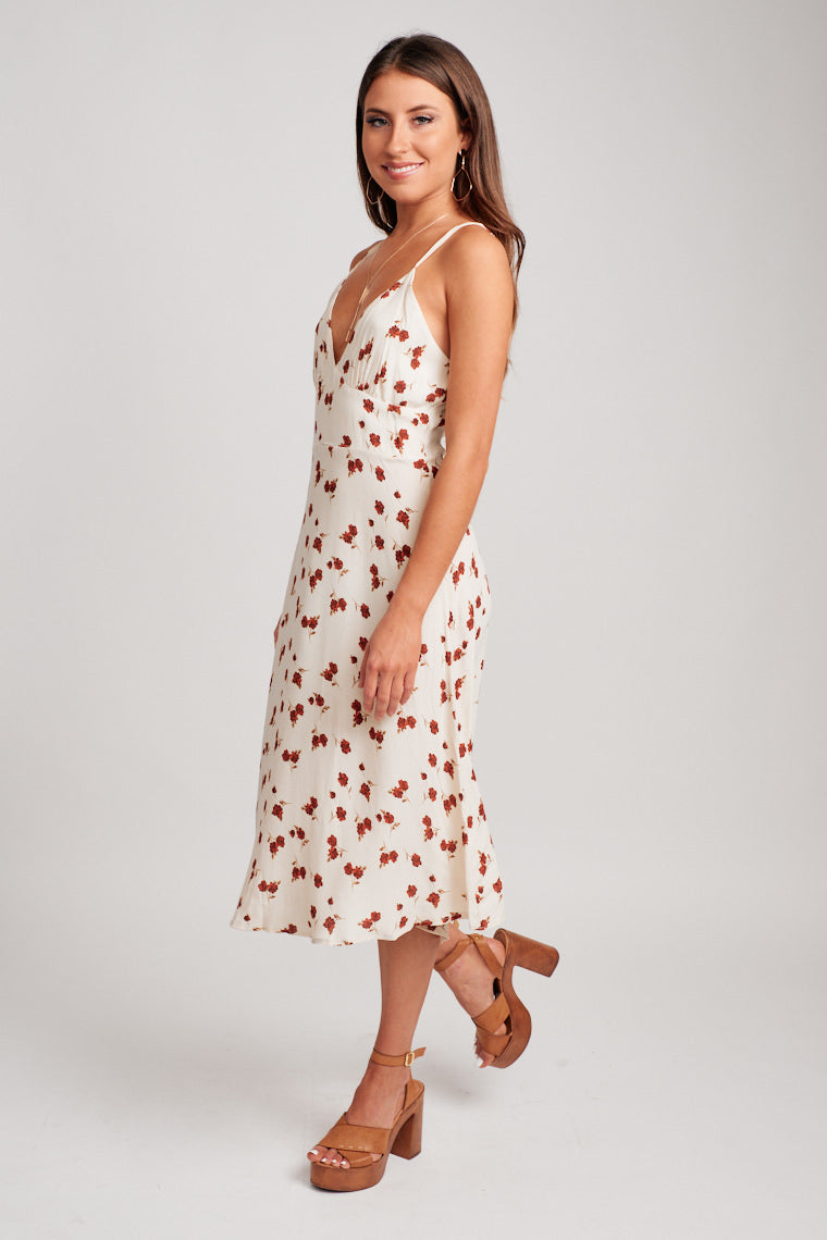 Thin adjustable straps that attach to a v-neckline and darted and fitted bodice and flow into a straight midi skirt with a gentle flair at the bottom.