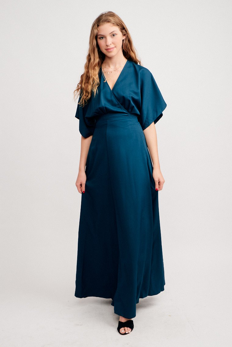 Short flowy sleeves attach to a surplice neckline on a darted bodice and lead to a skirt panel that ties at the side, flows down to a floor-touching and darted maxi skirt.