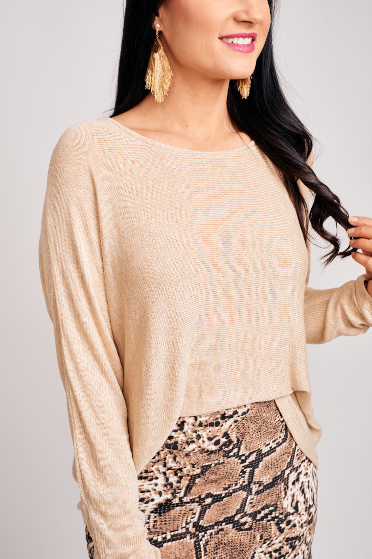 This light knit sweater has long sleeves that attach to a u-neckline and leads to an oversized and relaxed bodice silhouette. Pair with mid-rise jeans and booties.