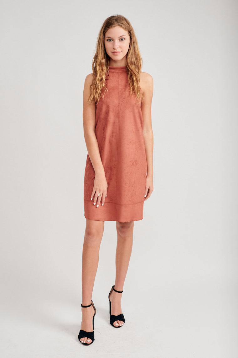 This sleeveless dress has a high banded neck that flows down into a comfortable shift silhouette with darted details down the dress and across the top and bottom hem.