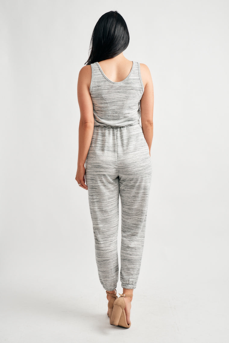 This casual and comfortable, everyday jumpsuit features a scoop neckline with a relaxed bodice atop a drawstring waist and jogger style pant legs.