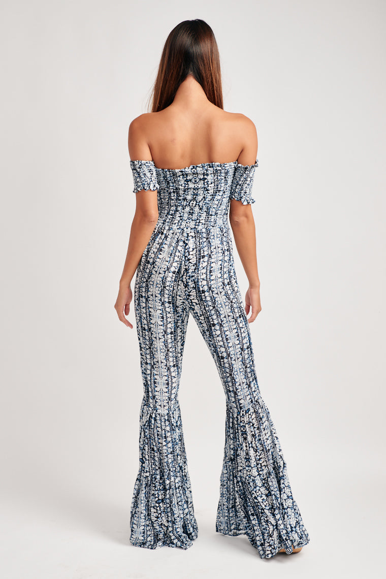 This fun and lively printed jumpsuit, strapless bodice with off the shoulder, smocked sleeves carries into a lightweight, flowy pant leg that flares at the ends.