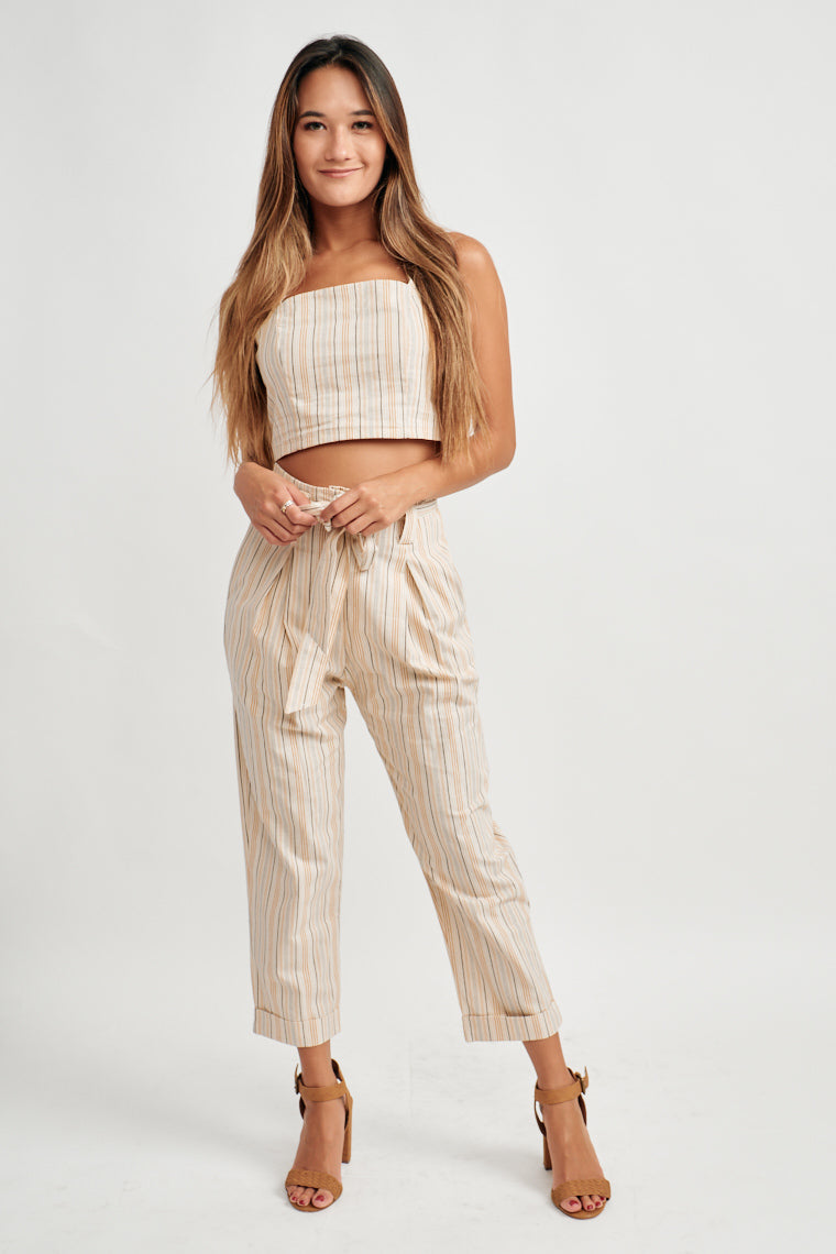 This beige crop top is decorated by black, tan and brown stripes. Thick straps, straight neckline with a fitted, seamed bodice with button details down the back.
